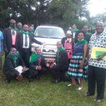 Kamerun Personen mit Auto auf Wiese
