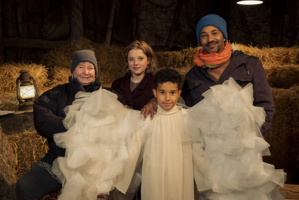 vier Schauspieler, einer als Engel verkleidet